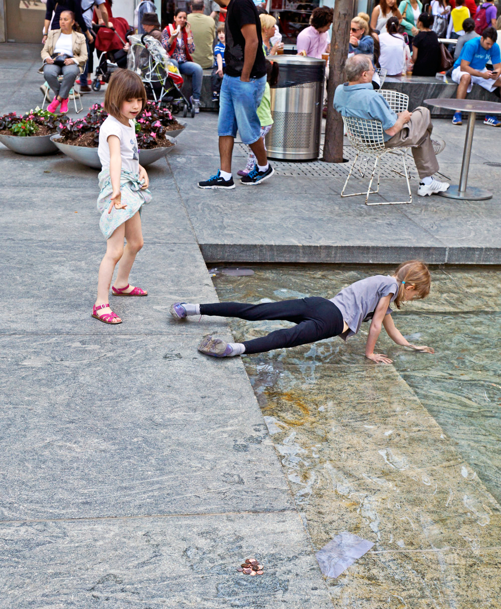 young girl fishing out pool pennies at the plaza
