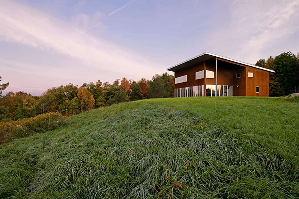 Modern 39 house on the hill 39 sits in an open meadow miles for Modern house on hill